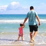 father and daughter on beach | summer health insurance